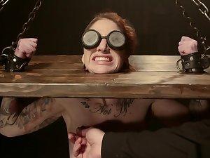 Blindfolded slave is locked in stocks